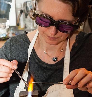 Anne-Sophie Chalut-Natal fabrique une perle en verre filé au chalumeau